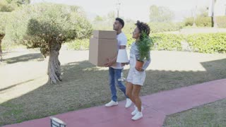 Young couple moving house carrying boxes and a potted houseplant along a walkway across a green lawn