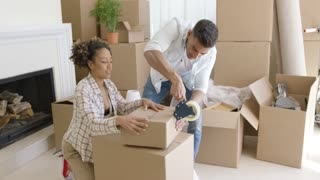 Young couple packing boxes to move home working as a team to tape up full cartons on the living room floor
