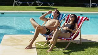 Young couple relaxing at a resort swimming pool sitting sunbathing on colorful deck chairs as they enjoy the hot summer sun on vacation