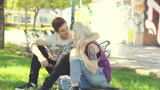 Young couple relaxing in an urban park sitting on the grass nuzzling and laughing affectionately together with a backdrop of colorful graffiti
