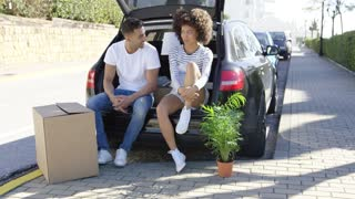 Young couple relaxing while moving house sitting in the open trunk of their estate car chatting with a carton on the ground in front of them.
