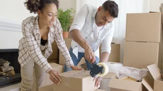 Young couple taping boxes as they pack up their home to move to a new house kneeling together on the floor working as a team