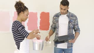 Young couple trying out different shades of paint to decorate their new apartment mixing it in a bucket and applying swatches to the wall