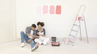 Young couple use tablet to discuss colors while sitting on floor beside bucket of paint and ladder