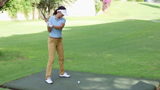 Young female golfer preparing to tee off at the start of a hole on a golf course with copy space on the fairway