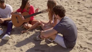 Young friends relaxing on a beach playing guitar