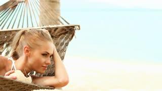 Young happy woman laying at hammock