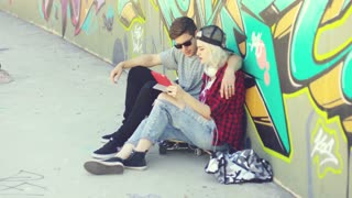 Young hipster couple browsing the internet on a tablet computer as they relax in the street sitting in front of a colorful graffiti covered wall