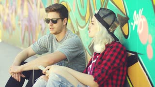 Young hipster couple relaxing against a colorful graffiti covered wall sitting on the sidewalk pointing and looking away from the camera to the side