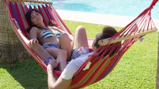 Young holiday couple relaxing in a hammock between two palm trees at a tropical resort with an inviting cool blue pool behind them