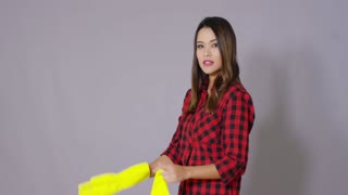 Young housewife putting on bright yellow rubber gloves as she prepares to do the housework upper body on grey