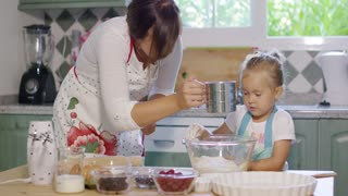 Young mother and daughter baking in the kitchen happily adding ingredients to a mixing bowl for a homemade berry pie