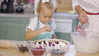 Young mother watching her little daughter baking as the little girl carefully places fresh berries on a freshly baked pastry crust with cream
