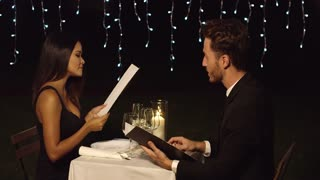Young romantic couple reading the menu to order their food on a night out together dining at an upscale restaurant