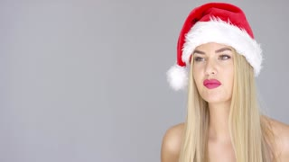 Young sexy woman in Santa Claus Christmas hat posing isolated on gray background. Smiling to the left side of the frame. She is bare shoulders.