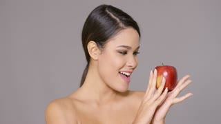 Young woman biting into a fresh red apple with her head turned to the side and eyes closed in anticipation in a healthy diet concept