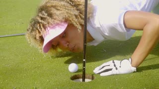 Young woman blowing her golf ball into the hole