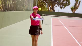 Young woman bouncing a ball on her tennis racket as she walks along the side of a court waiting to play a game