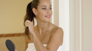 Young woman brushing her long brown hair tied in a pony tail as she stands in the bathroom wrapped in a clean white towel