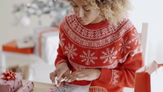 Young woman carefully wrapping a Christmas gift