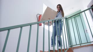 Young woman carrying a cardboard carton downstairs as she prepares to move house or do renovations