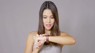 Young woman checking her wristwatch for the time with a serious expression head and shoulders on grey