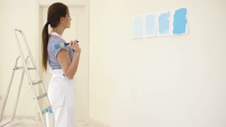 Young woman choosing a shade of blue paint from four swatches hung on the wall of her apartment as she starts renovating and redecorating