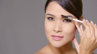 Young woman darkening her eyebrows applying makeup with a cosmetics brush in a close up cropped beauty facial portrait on grey with copy space