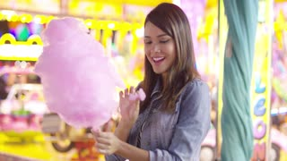 Young woman enjoying a bite of colorful pink spun sugar candy floss at a fair ground in a close up profile head shot