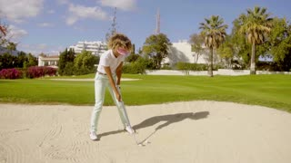 Young woman golfer playing out of a bunker
