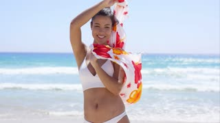 Young woman in a bikini standing on a beach holding a colorful sarong in her hands blowing in the breeze as she smiles at the camera.