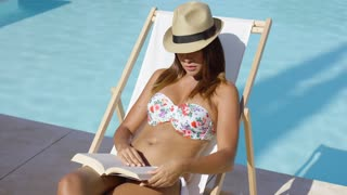 Young woman in a trendy hat and bikini relaxing in the sun on a deckchair alongside a pool reading a book