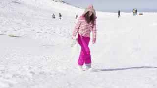 Young woman in pink snowsuit walking on ski slope with snowboard