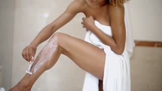 Young Woman Is Shaving Her Leg
