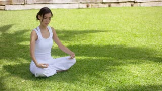 Young woman meditating in nature sitting cross-legged on green grass in the shade of a tree with her eyes closed and a tranquil expression
