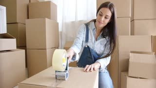 Young woman moving home packing brown cardboard boxes with a roll of tape in a close up view with stacked boxes behind her