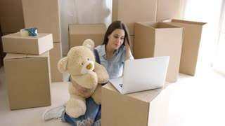Young woman moving house with her large cuddly plush teddy bear sitting o the floor typing on a laptop balanced on a brown packing carton