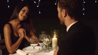 Young woman overcome when presented with a gift on a romantic night out with a beau at an upmarket restaurant