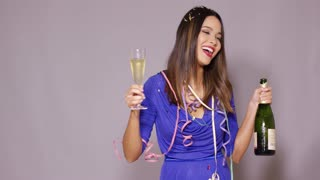 Young woman partying as she celebrates New Year with a bottle and glass of champagne in her hands laughing happily against a grey background with copy space.