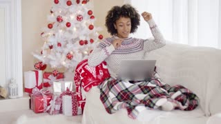 Young woman relaxing in front of the Christmas tree sitting under a rug on the sofa using her laptop computer gesturing with her hands
