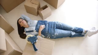 Young woman relaxing on the floor after packing up her home into cardboard boxes preparing for a move