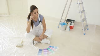 Young woman renovating or decorating her new home sitting on the floor looking at a collection of color swatches from a paint shop