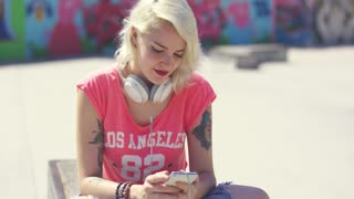 Young woman searching for tunes on her mobile as she sits on an urban wall in the sunshine with a pair of stereo headphones around her neck to listen to the music.