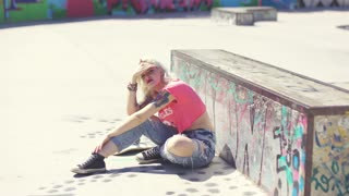 Young woman sitting in the hot sun waiting at a skate park with her skateboard in front of a graffiti covered wall shielding her eyes with her hand.
