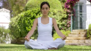 Young woman sitting in the lotus position on the grass meditating in a garden with a tropical villa behind her