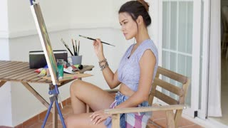 Young woman sitting on a wooden chair painting on a canvas displayed on an easel on her outdoor patio side view