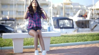 Young Woman Sitting On Bench In Harbor