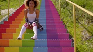 Young Woman Sitting On The Colorful Stairs.