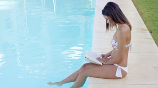 Young woman sitting on the edge dangling her feet in the water reading a book at the swimming pool