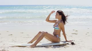 Young woman surfer in a bikini sitting on a surfboard on the beach looking out over the ocean watching the surf profile view